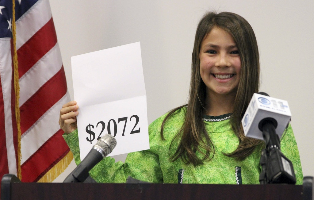 FILE - In this Monday, Sept. 21, 2015, file photo, student Shania Sommer of Palmer, Alaska, announces that nearly every Alaskan will receive $2,072 from the year's oil dividend check during a news conference in Anchorage, Alaska. Alaska lawmakers, faced with limited options for filling the state's budget deficit, may have to dip into earnings from Alaska's famed oil-wealth fund, with major proposals for doing so calling for changes to how the yearly checks that residents receive from fund earnings are calculated. (AP Photo/Mark Thiessen, File)