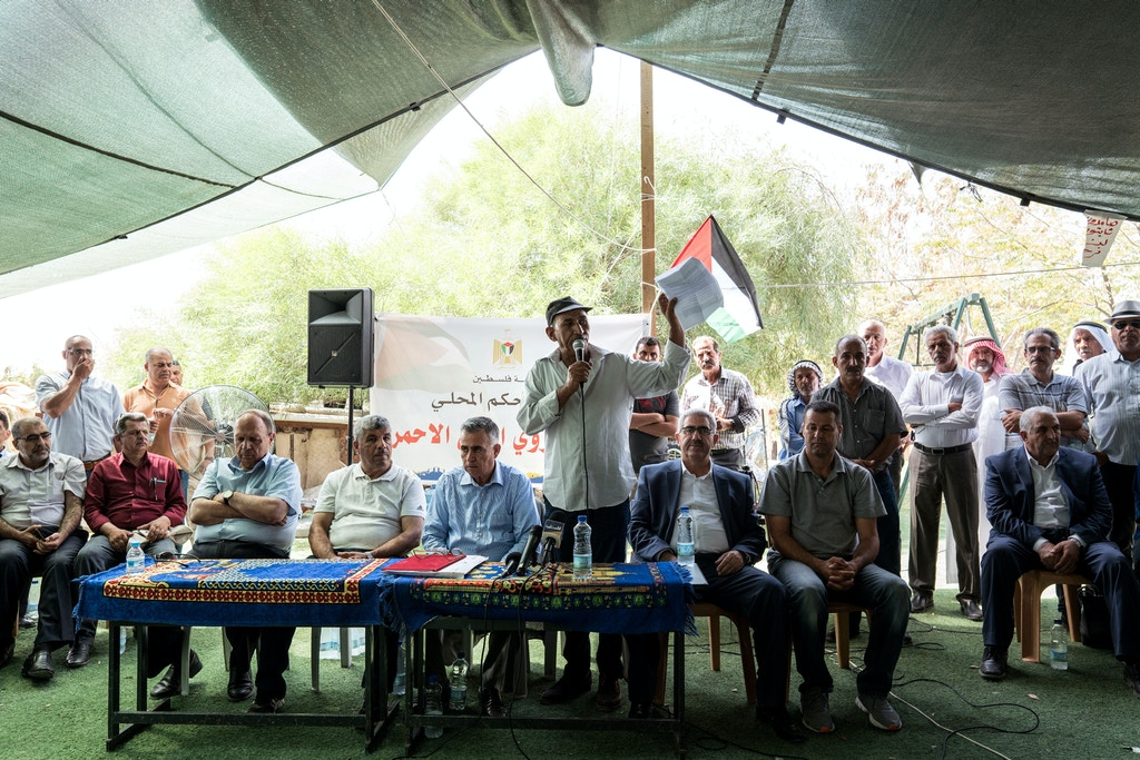 Abu Khamees (C) speaks during a press conference at the Al-Khan Al-Ahmar village on July 26, 2018.