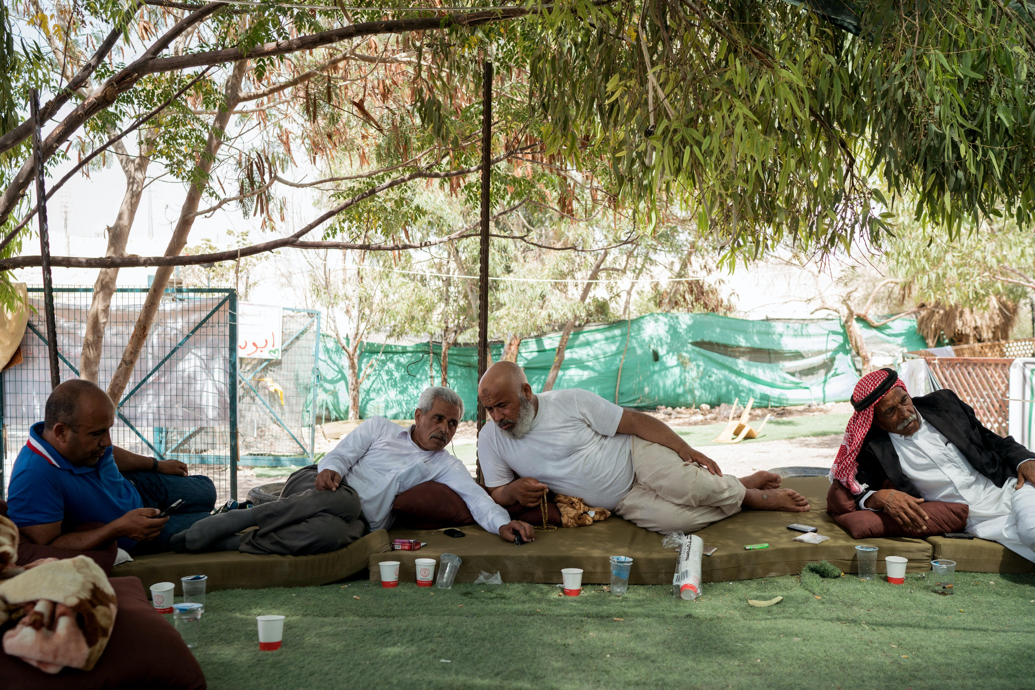 Palestinian Bedouin men sit together at the Al-Khan Al-Ahmar village on July 26, 2018.