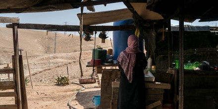 Palestinian Bedouin XXX washes dishes at her home in the village of Al-Khan Al-Ahmar on July 26, 2018