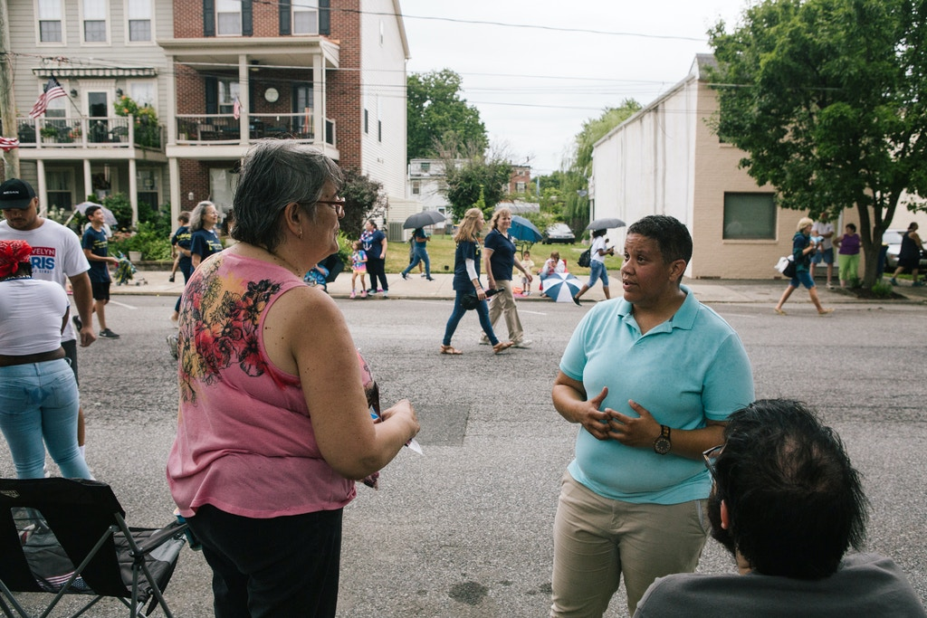 Kerri Evelyn Harris, Democratic candidate for the United States Senate from Delaware, stops to speak with residents while walking in a parade celebrating Delaware City Day in Delaware City, Delaware on Saturday, July 21, 2018. Harris, a former community organizer and Air Force veteran, is campaigning on issues such as Medicare-For-All, environmental justice, higher minimum wage, expanding LGBTQ rights, and pre-K for all. (Michelle Gustafson for The Intercept)