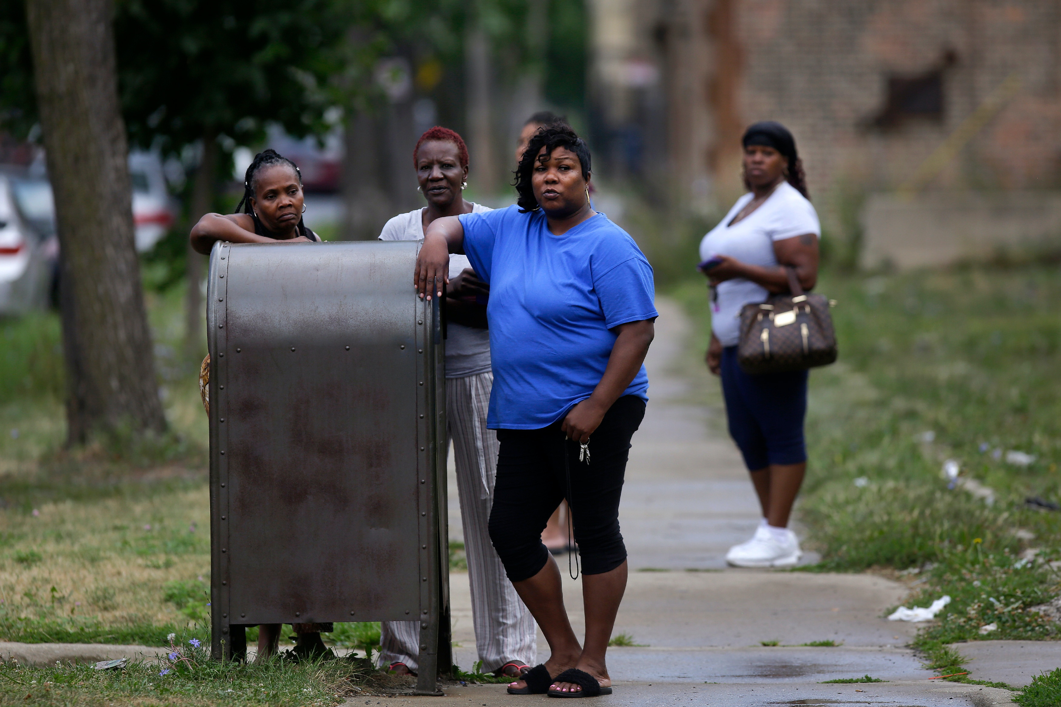 CHICAGO, IL - AUGUST 5 : Bystanders watch as Chicago Police officers and detectives investigate a shooting where multiple people were shot on Sunday, August 5, 2018 in Chicago, Illinois. In the last 24 hours over 30 people have been shot and at least 2 killed across Chicago including five mass shootings, where four or more victims were shot at one location. (Photo by Joshua Lott/Getty Images)