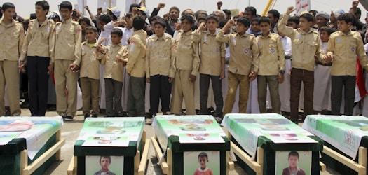 TOPSHOT - Des enfants yéménites se déchaînent contre Riyad et Washington le 13 août 2018 alors qu'ils participaient à un enterrement de masse dans la ville de Saada, au nord du Yémen, fief des rebelles Huthi soutenus par l'Iran. Coalition dirigée par l'Arabie saoudite la semaine dernière.  - Selon le Comité international de la Croix-Rouge, au moins 29 enfants ont été tués lors du raid aérien du 9 août sur un bus dans un marché bondé de Dahyan, dans la province de Saada.  (Photo par STRINGER / AFP) (Crédit photo devrait lire STRINGER / AFP / Getty Images)