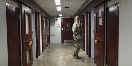 GUANTANAMO BAY, CUBA - OCTOBER 22: (EDITORS NOTE: Image has been reviewed by the U.S. Military prior to transmission.)   A U.S. soldier looks into a cell of the