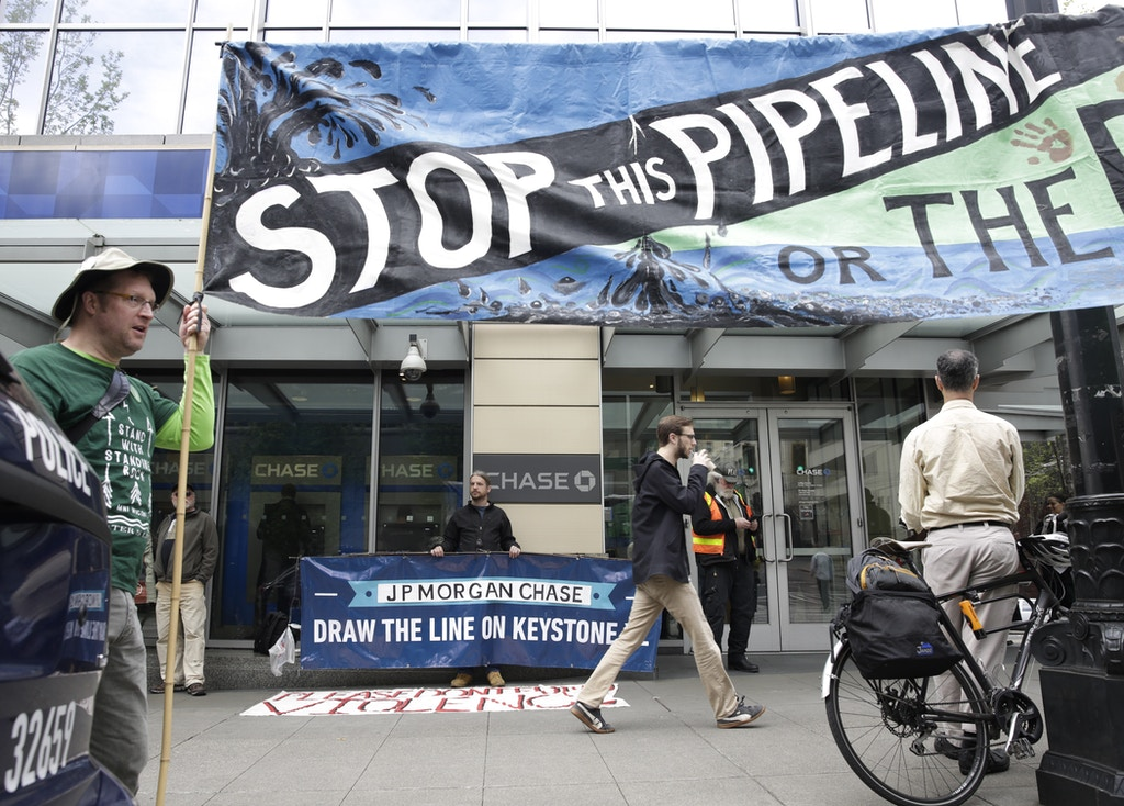 Indigenous leaders and climate activists disrupt business at a Chase Bank branch in Seattle on May 8, 2017. Demonstrators protested bank funding for the tar sands development and projects like the Keystone XL pipeline. / AFP PHOTO / Jason Redmond (Photo credit should read JASON REDMOND/AFP/Getty Images)