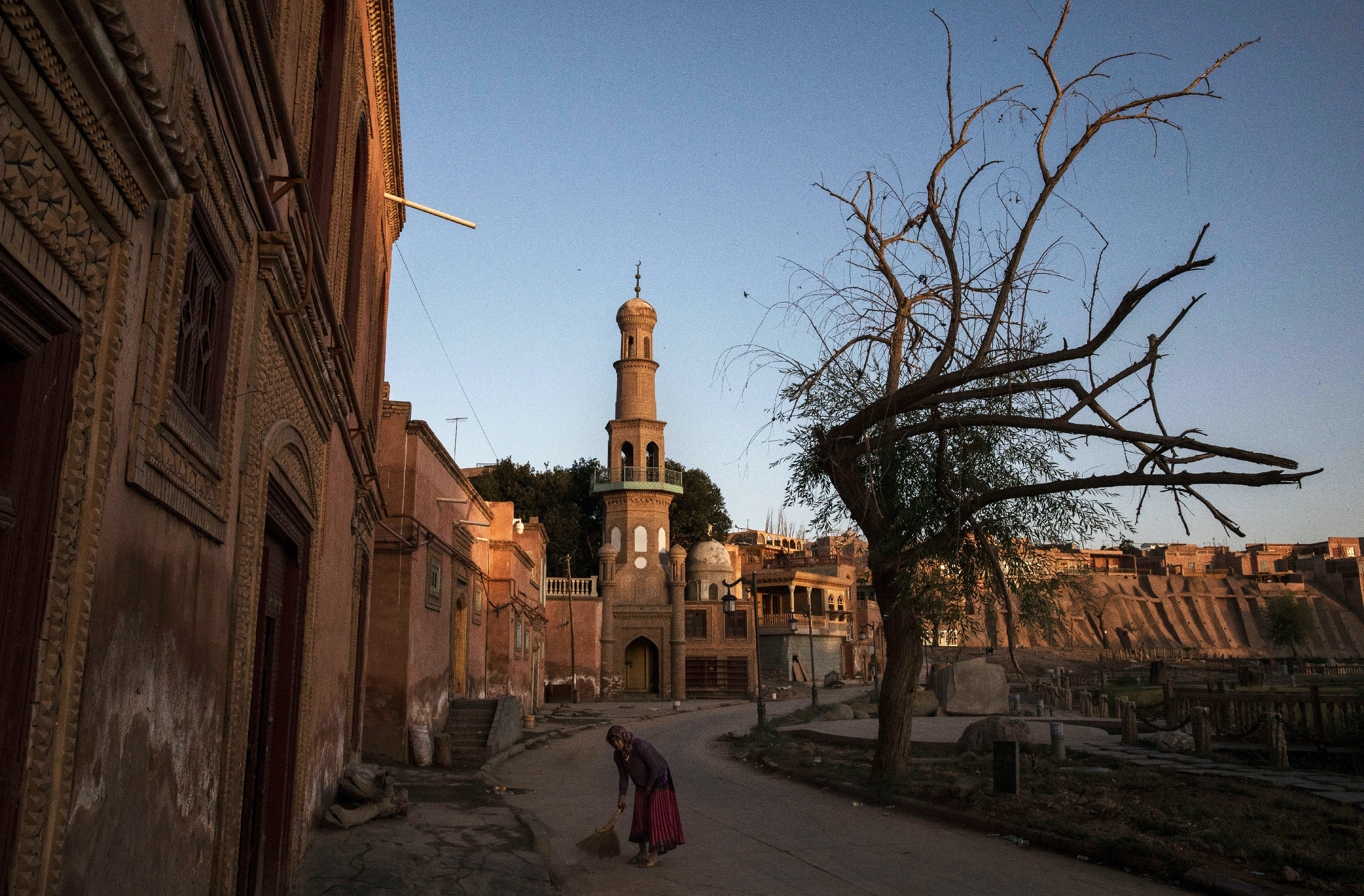 KASHGAR, CHINA - JULY 1: A ethnic Uyghur woman sweeps outside her house on July 1, 2017 in the old town of Kashgar, in the far western Xinjiang province, China. Kashgar has long been considered the cultural heart of Xinjiang for the province's nearly 10 million Muslim Uyghurs. At an historic crossroads linking China  to Asia, the Middle East, and Europe, the city has  changed under Chinese rule with government development, unofficial Han Chinese settlement to the western province, and restrictions imposed by the Communist Party. Beijing says it regards Kashgar's development as an improvement to the local economy, but many Uyghurs consider it a threat that is eroding their language, traditions, and cultural identity.  The friction has fuelled a separatist movement that has sometimes turned violent, triggering a crackdown on what China's government considers 'terrorist acts' by religious extremists.  Tension has increased with stepped up security in the city and the enforcement of measures including restrictions at mosques. (Photo by Kevin Frayer/Getty Images)