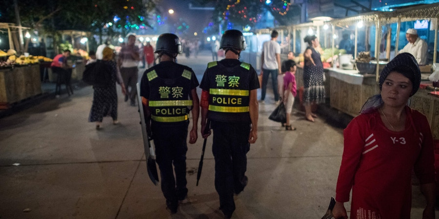 This picture taken on June 25, 2017 shows police patrolling in a night food market near the Id Kah Mosque in Kashgar in China's Xinjiang Uighur Autonomous Region, a day before the Eid al-Fitr holiday.The increasingly strict curbs imposed on the mostly Muslim Uighur population have stifled life in the tense Xinjiang region, where beards are partially banned and no one is allowed to pray in public. Beijing says the restrictions and heavy police presence seek to control the spread of Islamic extremism and separatist movements, but analysts warn that Xinjiang is becoming an open air prison. / AFP PHOTO / Johannes EISELE / TO GO WITH China-religion-politics, FOCUS by Ben Dooley (Photo credit should read JOHANNES EISELE/AFP/Getty Images)