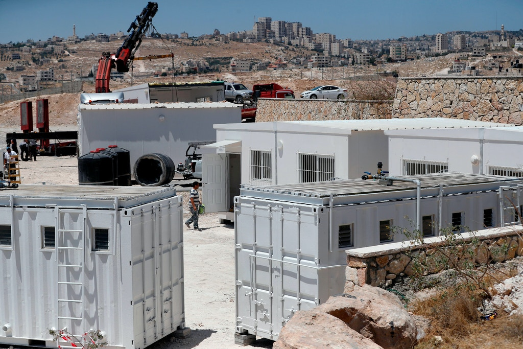 Israeli workers place container houses near the town of Al-Eizariyah in the occupied West Bank near East Jerusalem on July 9, 2018, to absorb residents of the Palestinian Bedouin village of Khan al-Ahmar who are set to be evicted from their homes. - Khan al-Ahmar, which Israeli authorities say was illegally constructed and the supreme court in May rejected a final appeal against its demolition, is located near several Israeli settlements along a road leading to the Dead Sea. (Photo by AHMAD GHARABLI / AFP)        (Photo credit should read AHMAD GHARABLI/AFP/Getty Images)