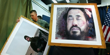 FILE - In this June 8, 2008, file photo, a U.S. soldier at a press conference in Baghdad, Iraq, takes down an older photo, to display a latest image purporting to show the body of Abu Musab al-Zarqawi, an al-Qaida-linked militant who led a bloody campaign of suicide bombings, kidnappings and hostage beheadings in Iraq. After al-Zarqawi's death in a 2006 U.S. airstrike, his Iraqi successor, Abu Omar al-Baghdadi, began to bring in more Iraqis, particularly former Saddam Hussein's officers. That process was accelerated when Abu Bakr al-Baghdadi took over after his predecessor was killed in a 2010 airstrike. (AP Photo/Khalid Mohammed, File)