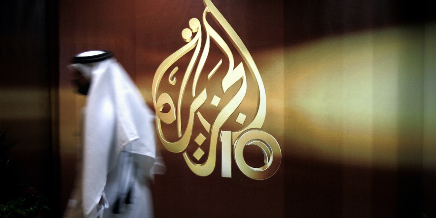 FILE -- In this Nov. 1, 2006 file photo, a Qatari employee of Al Jazeera Arabic language TV news channel walks past the logo of Al Jazeera in Doha, Qatar. Hackers allegedly broke into the website of Qatar's state-run news agency and published a fake story quoting the ruling emir, authorities there said Wednesday, May 24, 2017, as Saudi Arabia and the United Arab Emirates responded by blocking Qatari media, including broadcaster Al-Jazeera. (AP Photo/Kamran Jebreili, File)