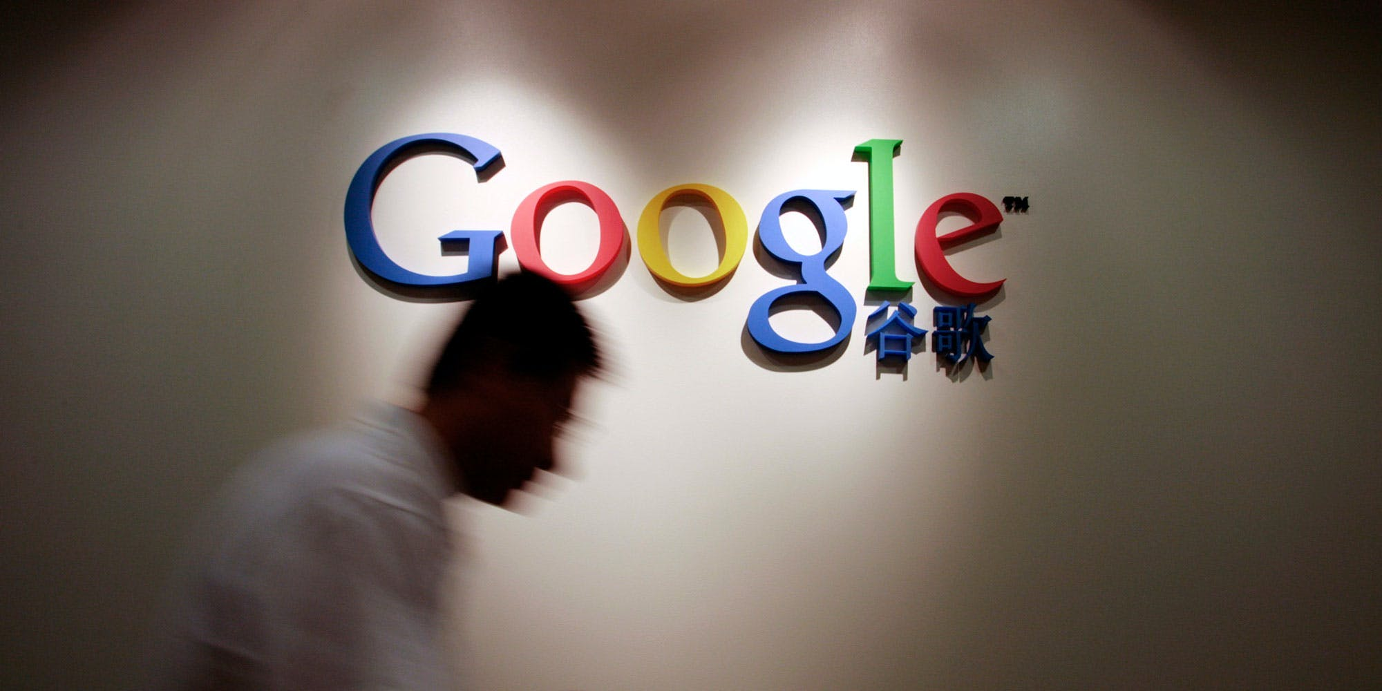 CHINA - AUGUST 15:  A member of Google Inc.'s China staff walks past the Google logo at their office in Shanghai on Wednesday, Aug. 15, 2007. When Thailand blocked Google Inc.'s YouTube Web site last year, the company dispatched deputy general counsel Nicole Wong to help restore access. In Bangkok, a sea of yellow shirts stunned her.  (Photo by Kevin Lee/Bloomberg via Getty Images)