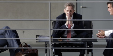 FILE-- In this Wednesday, Sept. 12, 2018 photo Hans-Georg Maassen, center, head of the German Federal Office for the Protection of the Constitution, waits for the beginning of a hearing at the home affairs committee of the German federal parliament, Bundestag, in Berlin, Germany. The leaders of Germany's three governing parties are meeting in Berlin on Tuesday to decide the fate of the country's domestic intelligence chief amid calls for him to be fired over his approach to far-right extremism. (AP Photo/Michael Sohn, file)