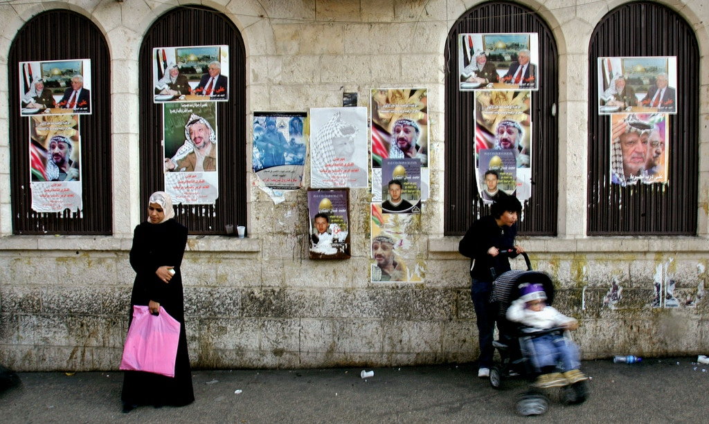 With portraits of late leader Yasser Arafat and Palestinian President Mahmoud Abbas hanging on the wall, a Palestinian woman, left waits in a line, not seen, in front of a cash machine to check if her salary had been deposited, in the West Bank town of Ramallah, Monday, Dec. 4, 2006. After Hamas won the Palestinian elections in January and took over the government, Western powers cut off aid to the Palestinian Authority because of the party's refusal to recognize Israel and renounce violence. The result has meant thousands of Palestinian civil servants have not received their salaries for months. (AP Photo/Muhammed Muheisen)