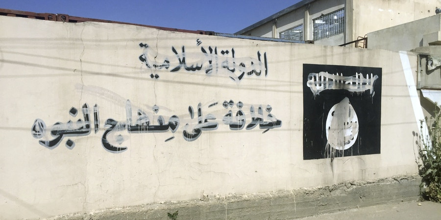 Picture of a wall with the logo and slogans of the ISIS terrorist militia - struck off by unknown people - taken in Mosul, Iraq, 09 May 2017. Photo by: Jan Kuhlmann/picture-alliance/dpa/AP Images
