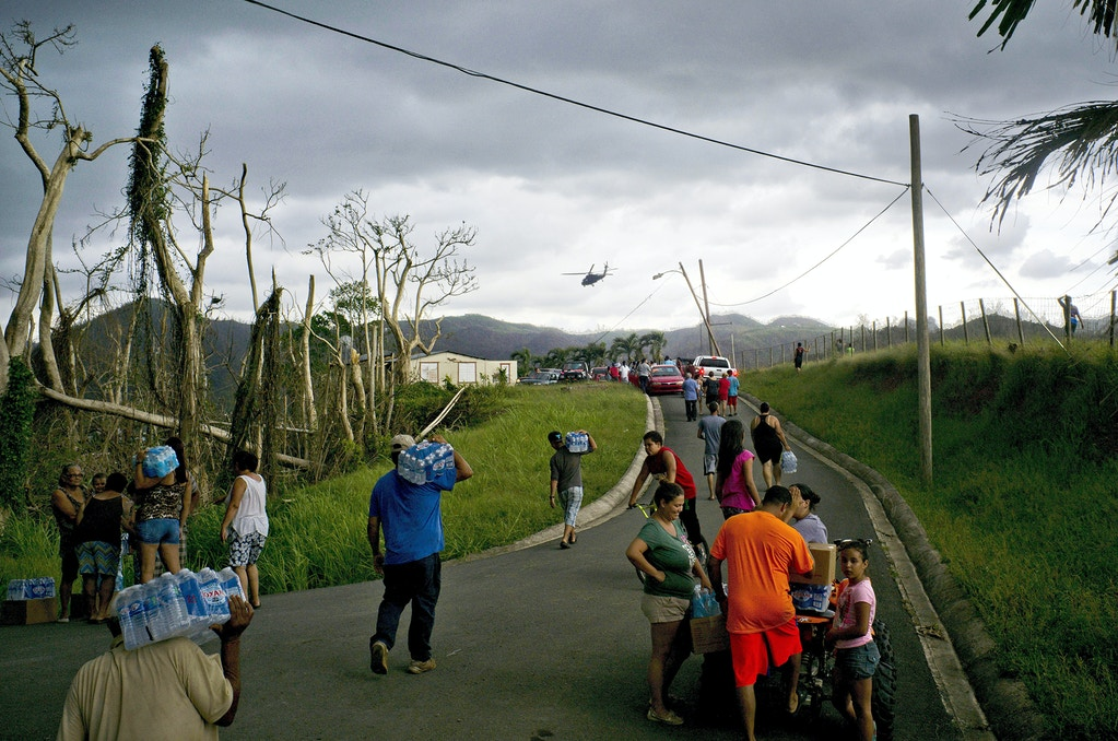 Victims of Hurricane Maria carry supplies brought to them via helicopter by the Puerto Rican National Guard at the  San Lorenzo neighborhood of Morovis, Puerto Rico, Saturday, Oct. 7, 2017. (AP Photo/Ramon Espinosa)