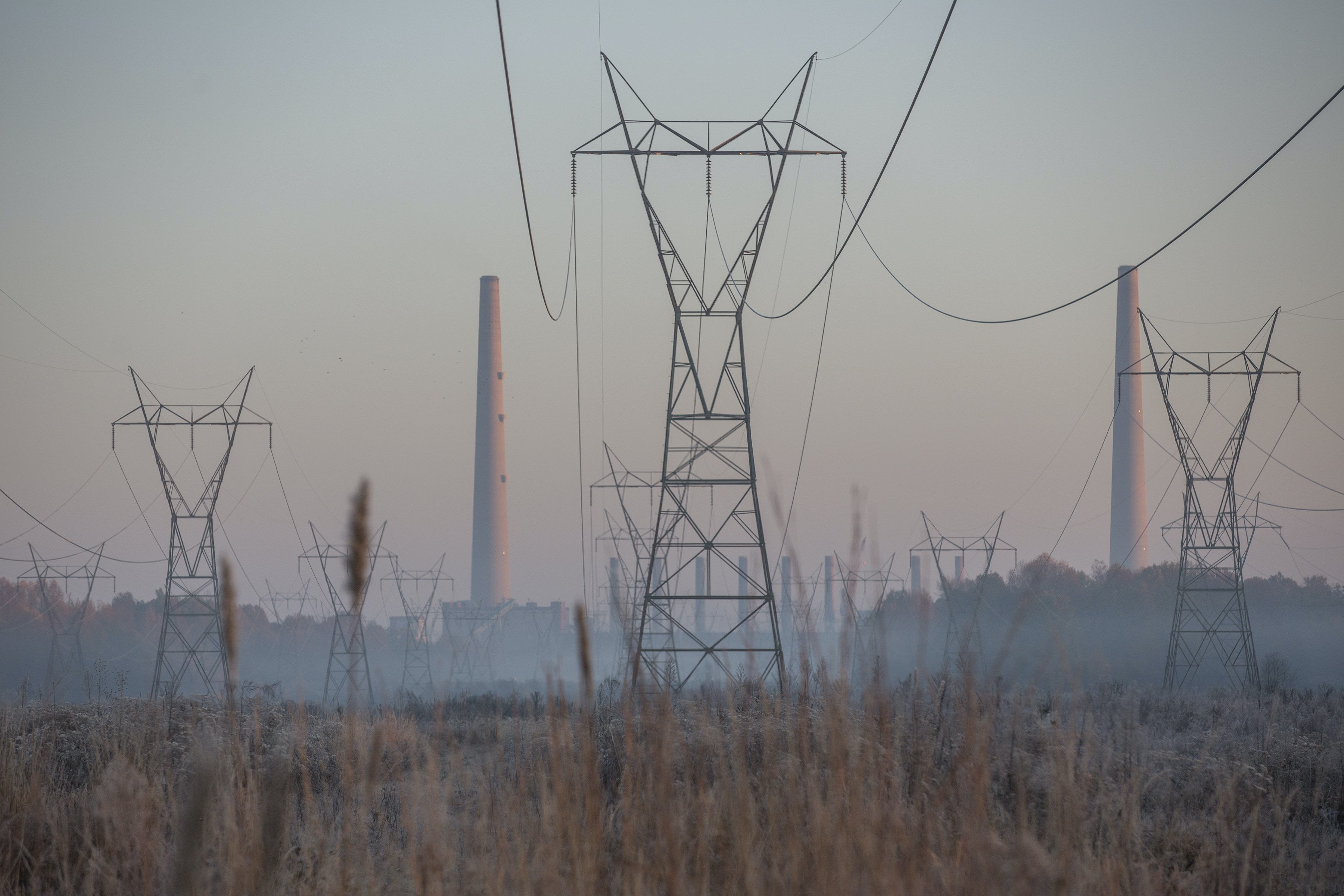 Transmission lines and Cooling towers at the TVA Shawnee Power Plant in West Paducah, Ky., are illuminated by the rising sun on Tuesday, Nov. 14, 2017. (Ryan Hermens/The Paducah Sun via AP)