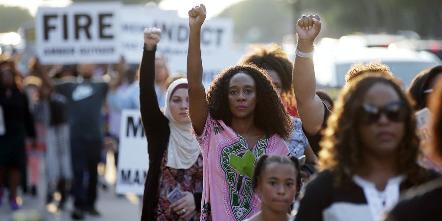 Demonstrators march around AT&T Stadium ahead of an NFL football game between the Dallas Cowboys and the New York Giants in protest of the recent killings of two black men by police, in Arlington, Texas, Sunday, Sept. 16, 2018. Botham Jean and O'Shae Terry were fatally shot by police in North Texas earlier in the month. (AP Photo/Brandon Wade)