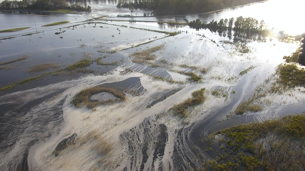 CORRECTS TO GRAY MATERIAL, NOT GRAY FLUIDS - In this image made from Friday Sept. 21, 2018 drone video provided by the N.C. Department of Environmental Quality, light gray material flows out of a flooded coal ash dump toward the Cape Fear River at Duke Energy's L.V. Sutton Power Station in Wilmington, N.C. Floodwaters from Hurricane Florence breached a dam at the plant's 1,100 reservoir on Saturday, Sept 22, 2018, flooding a dump containing 400,000 cubic yards (305,820 cubic meters) of coal ash. The gray ash left over when coal is burned to generate electricity contains mercury, lead, arsenic and other toxic heavy metals. (N.C. Department of Environmental Quality via AP)