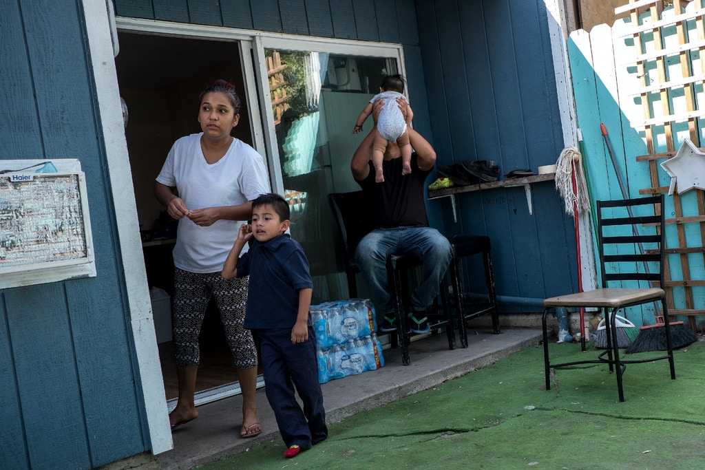 Heidi Cruz, 27, left, and her son Carlos Ismael, 5, second from left, watch as her son Brian Josue, 9, arrives home from school in Sacramento, Calif., Monday, Sept. 10, 2018. (Joel Angel Juárez for The Intercept)
