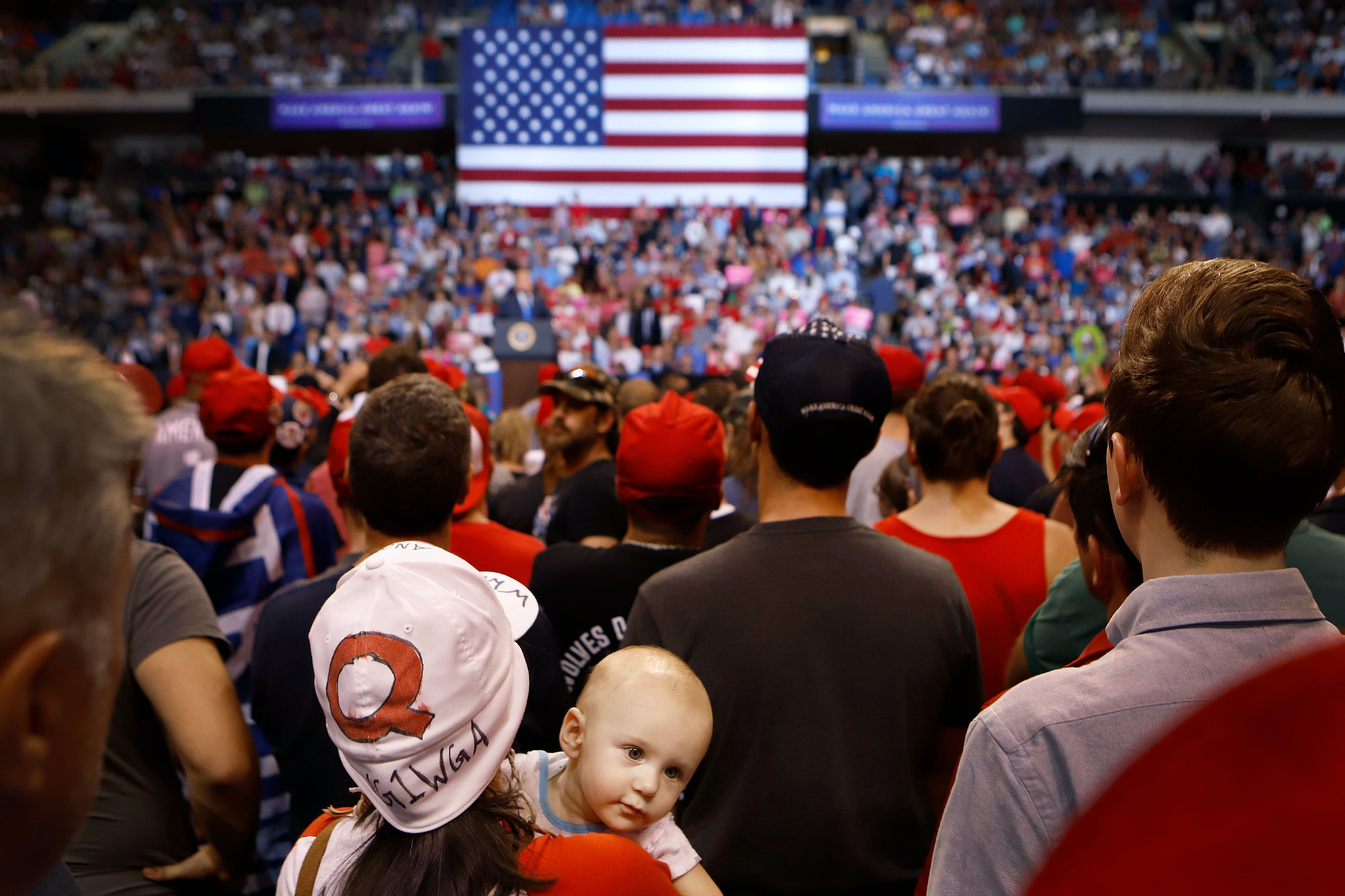 "WILKES BARRE, PA - AUGUST 02: Roxanne Kravitz, wearing a ""Q"" hat with her son Indigo, listen to President Donald J. Trump speak to a large crowd on August 2, 2018 at the Mohegan Sun Arena at Casey Plaza in Wilkes Barre, Pennsylvania. ""Q"" represents QAnon, a conspiracy theory group that has been seen at recent rallies.  (Photo by Rick Loomis/Getty Images)"