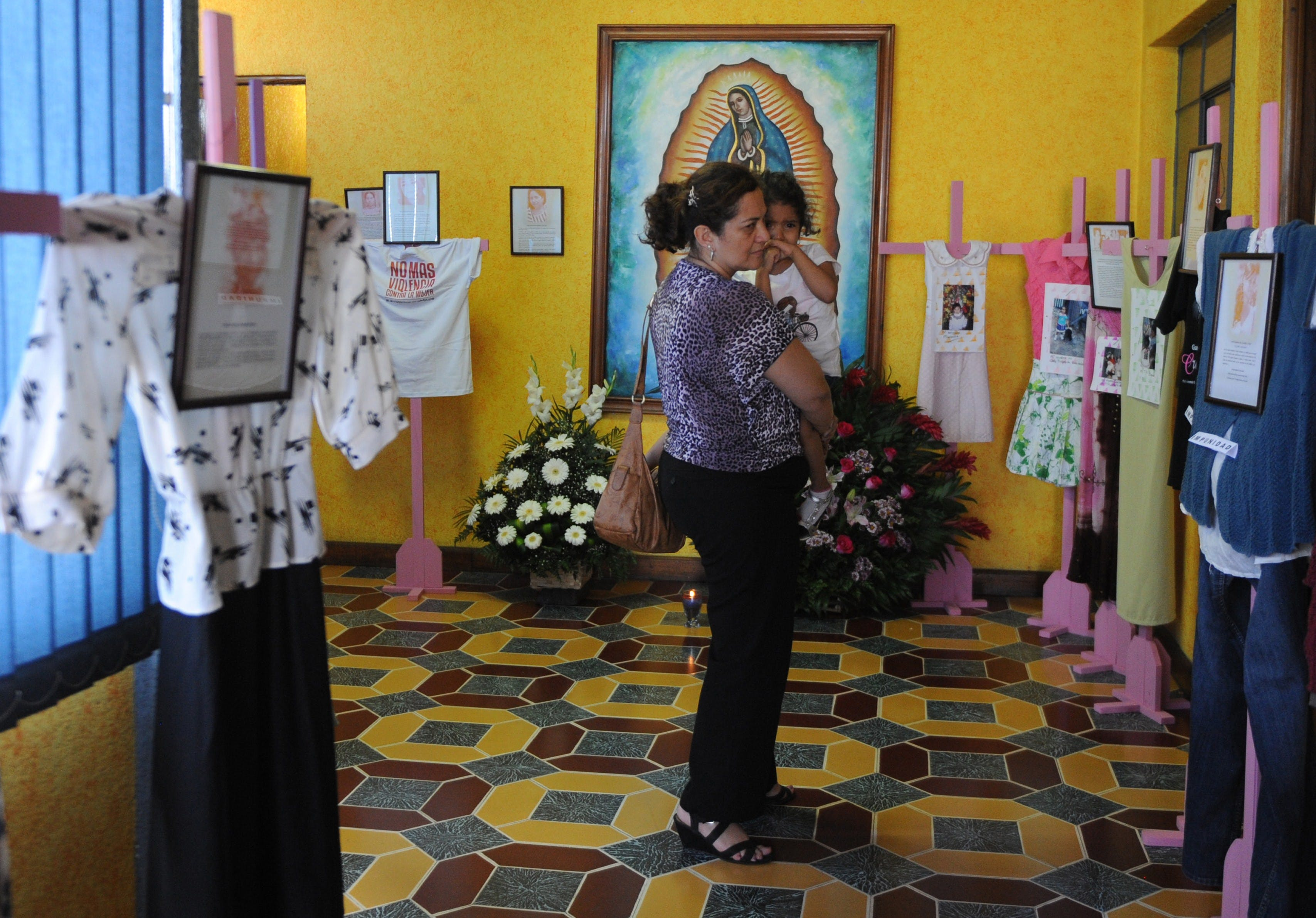 A woman and her daughter look at crosses displaying clothes of women victims of violence during a tribute at the headquarters of the Survivors Foundation in Guatemala City on November 23, 2014, in the framework of the Day for the Elimination of Violence against Women.  AFP PHOTO/Johan ORDONEZ        (Photo credit should read JOHAN ORDONEZ/AFP/Getty Images)