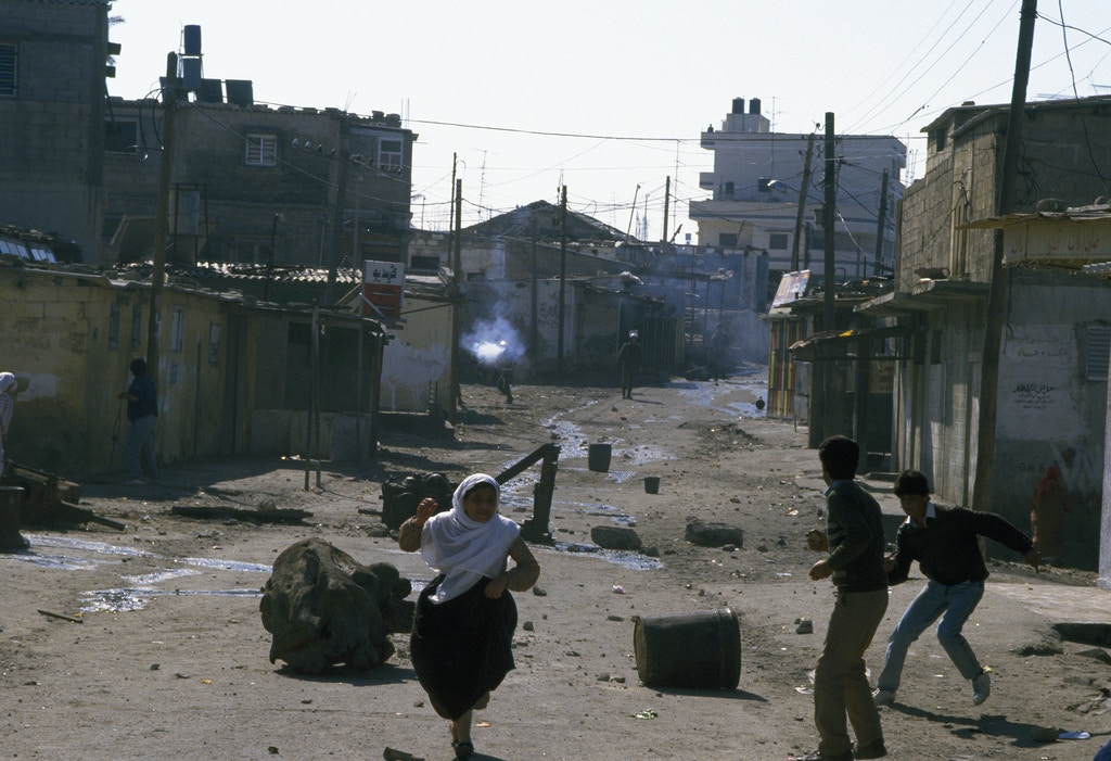 Civilians flee gunfire from armed soldiers after violence broke out after rebel Israeli and Palestinian fighters protested during the First Intifada on Feb. 2, 1988 in Gaza, Palestine.