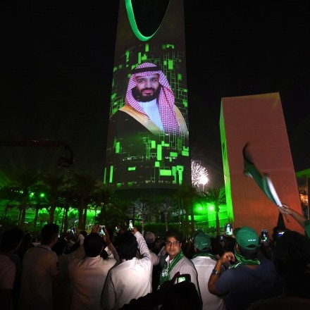 People watch a projection depicting a portrait of Crown Prince Mohammed bin Salman during an event in the capital Riyadh on late September 23, 2017 commemorating the anniversary of the founding of the kingdom.The national day celebration coincides with a crucial time for Saudi Arabia, which is in a battle for regional influence with arch-rival Iran, bogged down in a controversial military intervention in neighbouring Yemen and at loggerheads with fellow US Gulf ally Qatar. / AFP PHOTO (Photo credit should read /AFP/Getty Images)