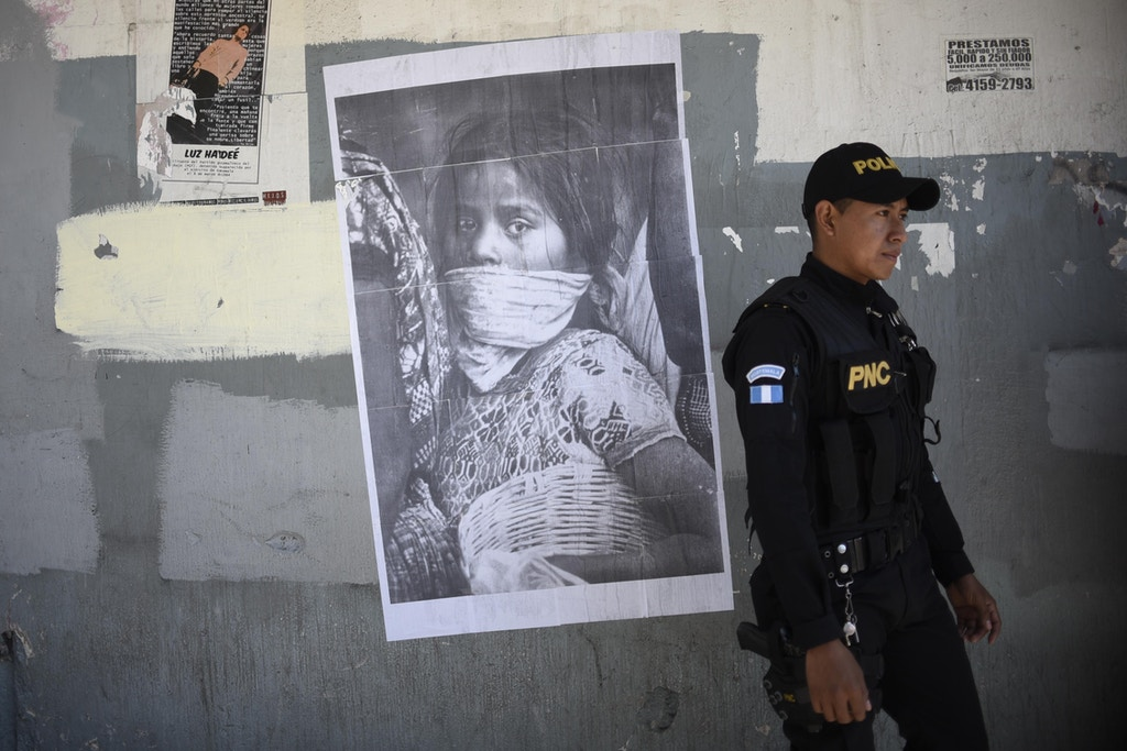 TOPSHOT - A police officer stands next to a poster during a march to mark International Women's Day in Guatemala City on March 8, 2018. / AFP PHOTO / Johan ORDONEZ (Photo credit should read JOHAN ORDONEZ/AFP/Getty Images)