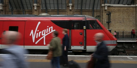 Rail passengers pass a train operated by Virgin Trains East Coast main line service are at London Kings Cross rail station in London on May 16, 2018. - The British government announced on Wednesday that it would resume control of the East Coast Main Line rail service, privatised three years ago, following the termination of the franchise agreement with Virgin Trains East Coast (VTEC) - a joint venture between Stagecoach and Virgin. Trains will continue to run by the Department for Transport (DfT) through an operator of last resort (OLR). (Photo by Daniel LEAL-OLIVAS / AFP)        (Photo credit should read DANIEL LEAL-OLIVAS/AFP/Getty Images)