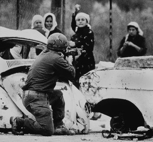 An Israeli soldier takes aim as a Palestinian woman hurls a rock at him during a demonstration in which one Palestinian youth was shot dead several months after the outbreak of the intifada on Feb. 29, 1988 in Gaza, Palestine.