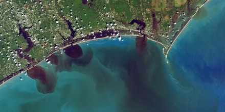 An image from Landsat 8 shows how soil, pollution, and other debris had discolored the water in swollen bodies of water along the coast of North Carolina, and into the ocean, on Sept. 20, 2018.
