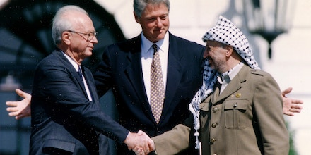 PLO Chairman Yasser Arafat (R) shake hands with Israeli Prime Minister Yitzhak Rabin (L), as U.S. President Bill Clinton stands between them, after the signing of the Israeli-PLO peace accord, at the White House in Washington September 13, 1993. REUTERS/Gary Hershorn (UNITED STATES - Tags: POLITICS) - GM1E99D1UCK01