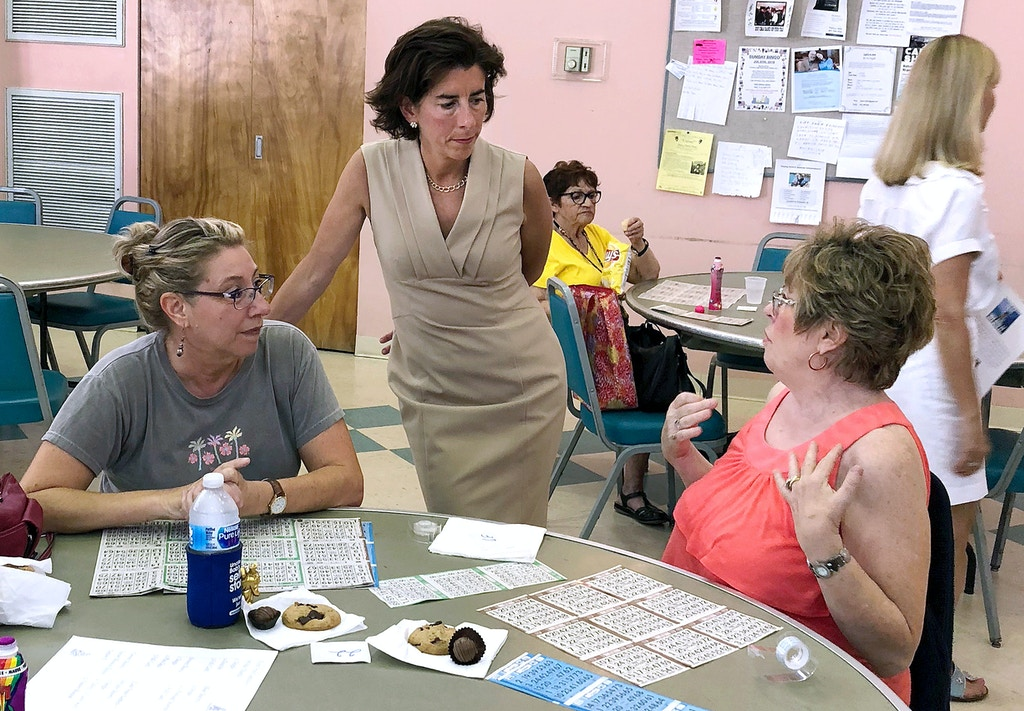 FILE- In this Aug. 2, 2018, file photo, Rhode Island Gov. Gina Raimondo, center, speaks with Lisa McGovern, left, and Betty Toye at the Pilgrim Senior Center in Warwick, R.I. Raimondo and U.S. Rep. Gwen Graham of Florida are among nine women running for governor who will face primary voters in coming weeks. No more than nine women have ever led states at the same time. (AP Photo/Michelle R. Smith, File)