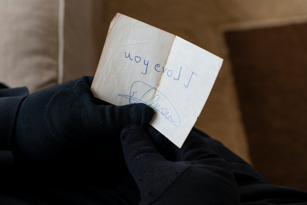 "A hand written note from Sandy Sulzle's husband, Shawki Omar, that says "" I love you "" flipped, to be viewed as a mirror reflection. A note he wrote for her 30 years ago and she keeps in her purse at all time."