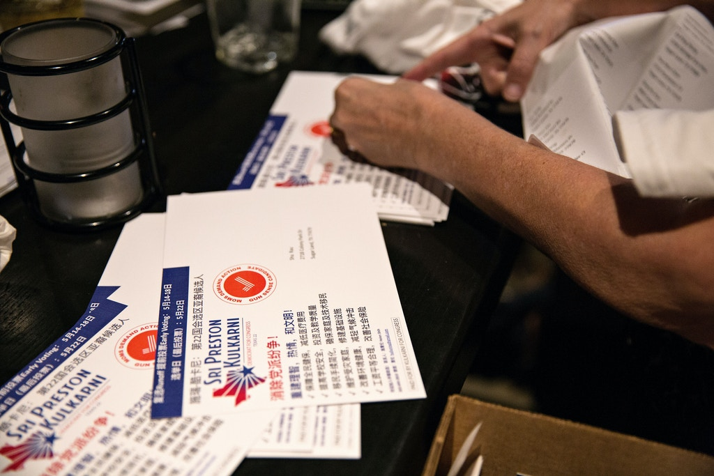 Campaign volunteers of Sri Preston Kulkarni place address labels on postcard mailers during a Rockets watch party at Bar Louie in Sugar Land, Texas.