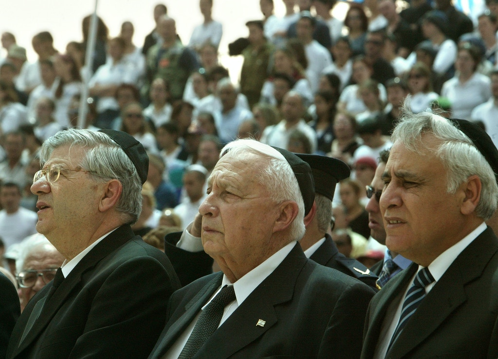 Marking Israeli Memorial Day, Israeli Prime Minister Ariel Sharon, flanked on the right by Israeli President Moshe Katsav, and on the left by Israeli Supreme Court Chief Justice Aharon Barak, participates in a memorial ceremony for Israeli civilians, including terror victims, who have been killed since Israel's founding 56 years ago, at Mt. Herzl Cemetery, in Jerusalem, Monday, April 26, 2004. (AP Photo/Brennan Linsley)