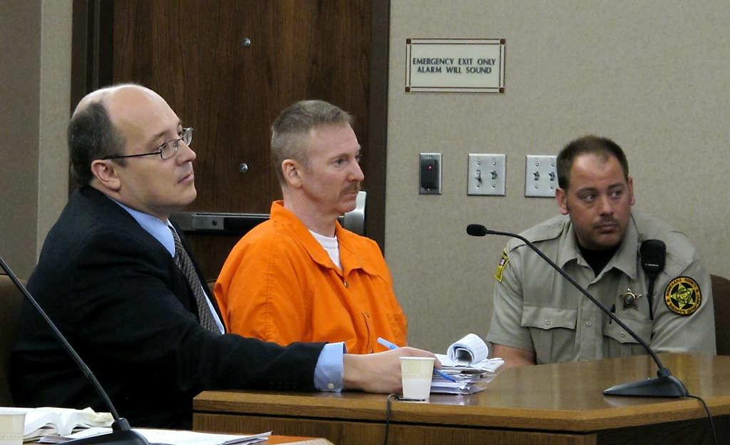 "Eric Robert, center, and his defense lawyer, Mark Kadi, listen to Judge Brad Zell read the sentence for Robert's killing senior corrections officer Ronald ""R.J."" Johnson during a failed escape attempt in Sioux Falls, S.D., Thursday, Oct. 27, 2011. Robert was given the death penalty. (AP Photo/Argus Leader, Devin Wagner)"