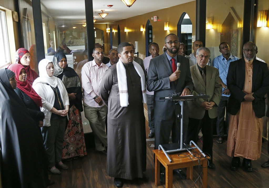 Council on American-Islamic Relations-Minnesota Executive Director Jaylani Hussein, center with microphone, speaks to growing Somali community concerns about the proposed government-initiated Countering Violent Extremism (CVE) program during a news conference, Thursday, Aug. 6, 2015, in Minneapolis. Muslim groups and civil rights activists across the nation are calling for greater transparency in the program by President Barack Obama's administration. (AP Photo/Jim Mone)