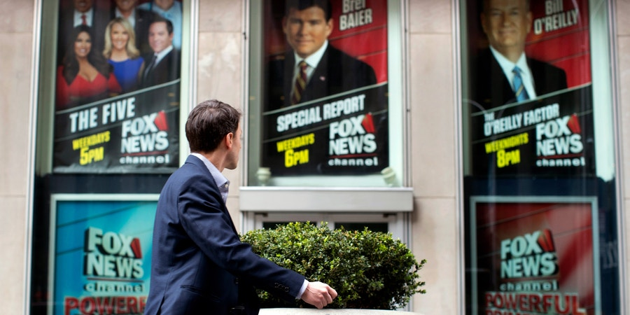 A pedestrian walks past the News Corp. headquarters building in New York displaying posters featuring Fox News Channel personalities including Bill O'Reilly, right, on Wednesday, April 19, 2017. O'Reilly has lost his job at Fox News Channel following reports that five women had been paid millions of dollars to keep quiet about harassment allegations. 21st Century Fox issued a statement Wednesday that
