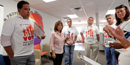 In this April 18, 2018 photo, Betsy Franceschini, second from left, senior state director of the Florida Southeast Hispanic Federation, briefs a group of canvassers before they go out to register hispanic voters in Orlando, Florida. While Puerto Ricans are U.S. citizens, they cannot vote in the presidential election while on the island, which is a territory not a state, but their vote has the same weight as other Americans when they move to the mainland, as hundreds of thousands have done over the past decade, first because of a deep economic recession and then because of Hurricane Maria. (AP Photo/John Raoux)