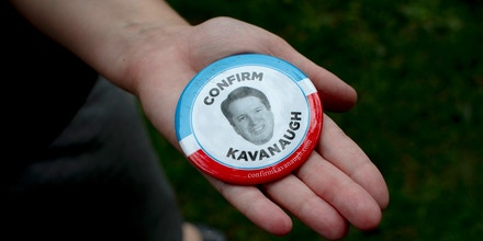 A demonstrator holds a 'confirm Kavanaugh' button at a rally in support of the Senate confirmation of Judge Brett Kavanaugh in Washington, D.C. on Sept. 27, 2018.