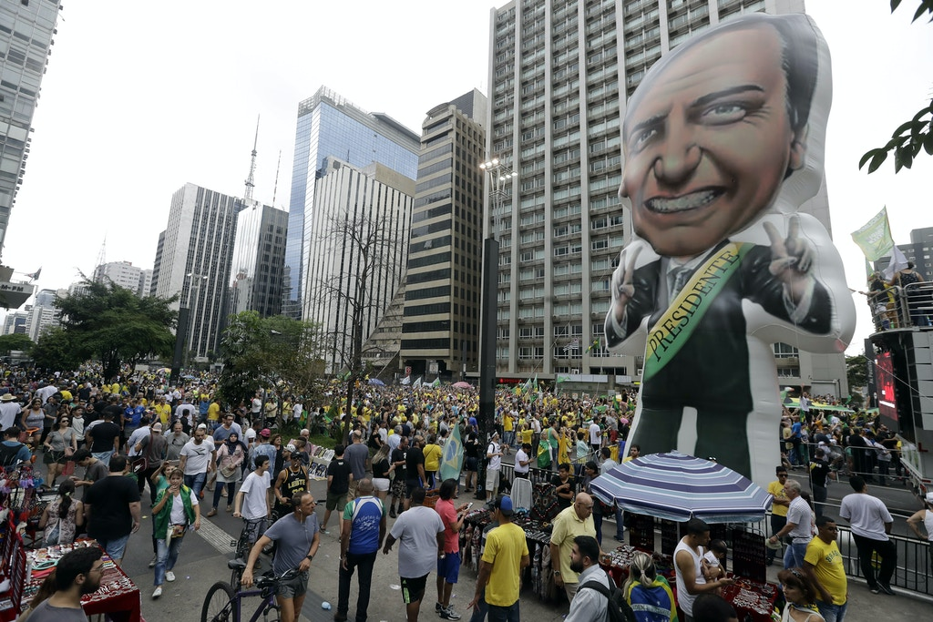A large, inflatable doll of presidential candidate Jair Bolsonaro, with the National Social Liberal Party, stands during a rally along Paulista Avenue in Sao Paulo, Brazil, Sunday, Sept. 30, 2018. Brazil will hold general elections on Oct. 7. (AP Photo/Andre Penner)