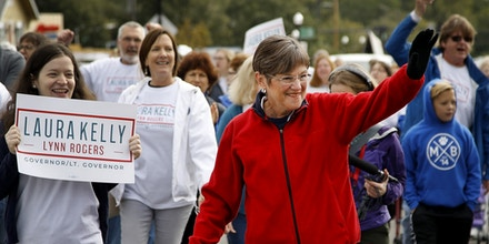 Democratic candidate for Kansas Governor, Laura Kelly walks with supporters during the Overland Park fall festival parade Saturday, Sept. 29, 2018, in Overland Park, Kan. (AP Photo/Charlie Riedel)