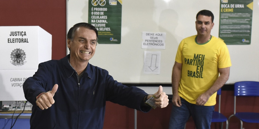 07 October 2018, Brazil, Rio de Janeiro: 07 October 2018, Brazil, Sao Paulo: Jair Bolsonaro (L), ultra-right candidate for the post of Brazilian president, laughs after casting his vote at a polling station in the city school Rosa da Fonseca, in Vila Militar, west of the city. In the background is his son Flavio Bolsonaro. In the midst of a severe crisis, the presidential election has begun in Brazil. Photo by: Fabio Teixeira/picture-alliance/dpa/AP Images
