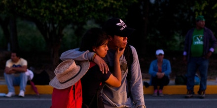 A young migrant couple embraces as they wait in hope of getting a ride from a passing truck, between Pijijiapan and Tonala, Mexico, at sunrise on Friday, Oct. 26, 2018. Many migrants said they felt safer traveling and sleeping with several thousand strangers in unknown towns than hiring a smuggler or trying to make the trip alone.(AP Photo/Rebecca Blackwell)