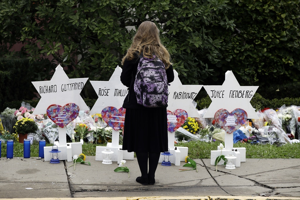 A person stands in front of Stars of David that are displayed in front of the Tree of Life Synagogue with the names of those killed in Saturday's deadly shooting in Pittsburgh, Monday, Oct. 29, 2018. (AP Photo/Matt Rourke)