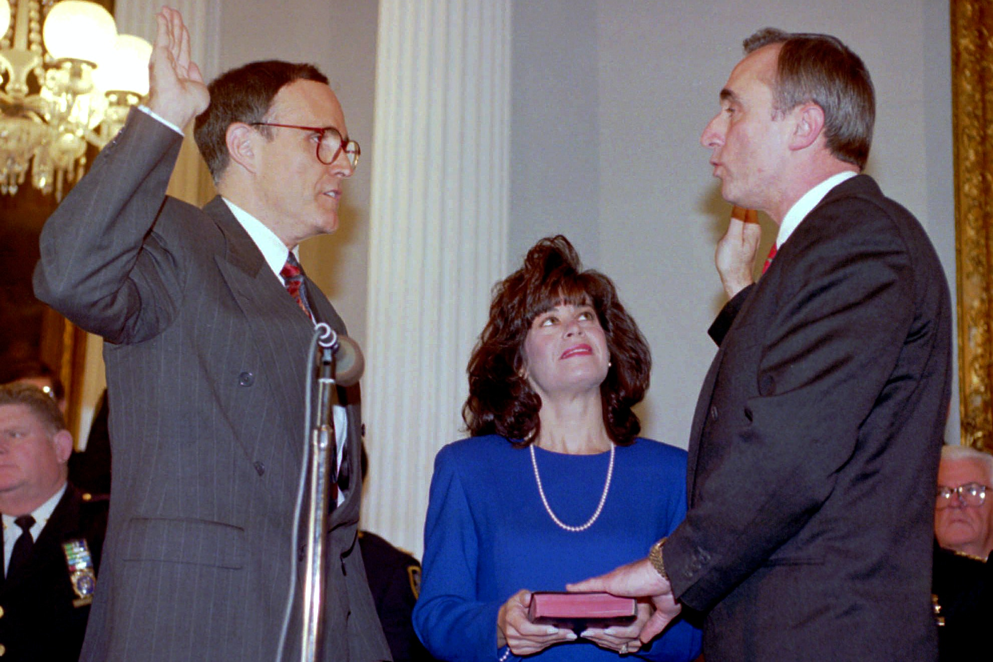 New York City Mayor Rudolph Giuliani, left, adminsters the oath of office to Police Commissioner William J. Bratton at New York City Hall ceremonies Tuesday, Jan. 11, 1994. Bratton's wife, Cheryl Fiandaca, holds the Bible for the former Boston police commissioner. (AP Photo/Richard Drew)