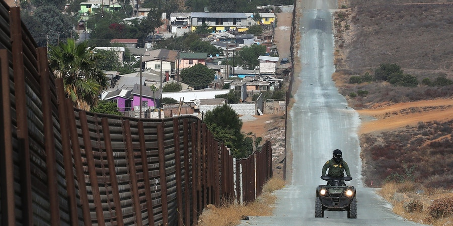 SAN DIEGO, CA - JULY 16:  A U.S. Border Patrol agent patrols along a section of the U.S.-Mexico border fence on July 16, 2018 in San Diego, California. The entire Southwest border saw 34,114 U.S. Border Patrol apprehensions in the month of June compared with 40,338 in May.  (Photo by Mario Tama/Getty Images)