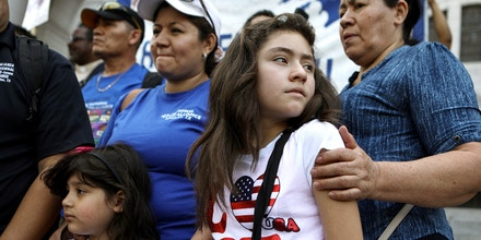 LOS ANGELES, CA - AUGUST 17:  Mother Mily Rivas (TOP CENTER L), a TPS recipient from El Salvador, stands with her daughters Suri and Ariely Murrilo, both U.S. citizens, at the launch of the 'TPS Journey for Justice Caravan' outside City Hall on August 17, 2018 in Los Angeles, California. Mily faces deportation with the termination of the TPS program for Salvadorans. The caravan protests the Trump administration's termination of Temporary Protected Status- a federal program which protects 450,000 immigrants from certain countries from deportation. The caravan will travel from Los Angeles to Washington, DC with more than 50 current Temporary Protected Status (TPS) holders. (Photo by Mario Tama/Getty Images)