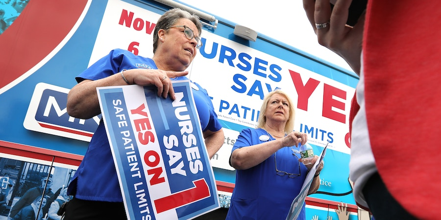 SOMERVILLE, MA - AUGUST 21: Karen Coughlin, left, and Donna Kelly-Williams, president of the Massachusetts Nurses Association, chat following a nurses rally near Partners HealthCare in Somerville, MA on Aug. 21, 2018. The MNA backs ballot initiative #1, that mandates minimum levels of nurse staffing statewide. (Photo by Pat Greenhouse/The Boston Globe via Getty Images)